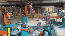 Robotizované pracoviště se dvěma spolupracujícími roboty.